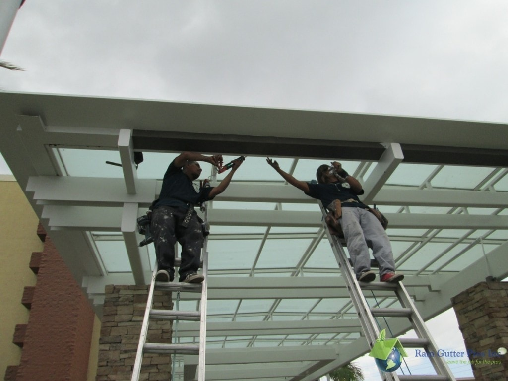 Two man industrial contractor gutter installation
